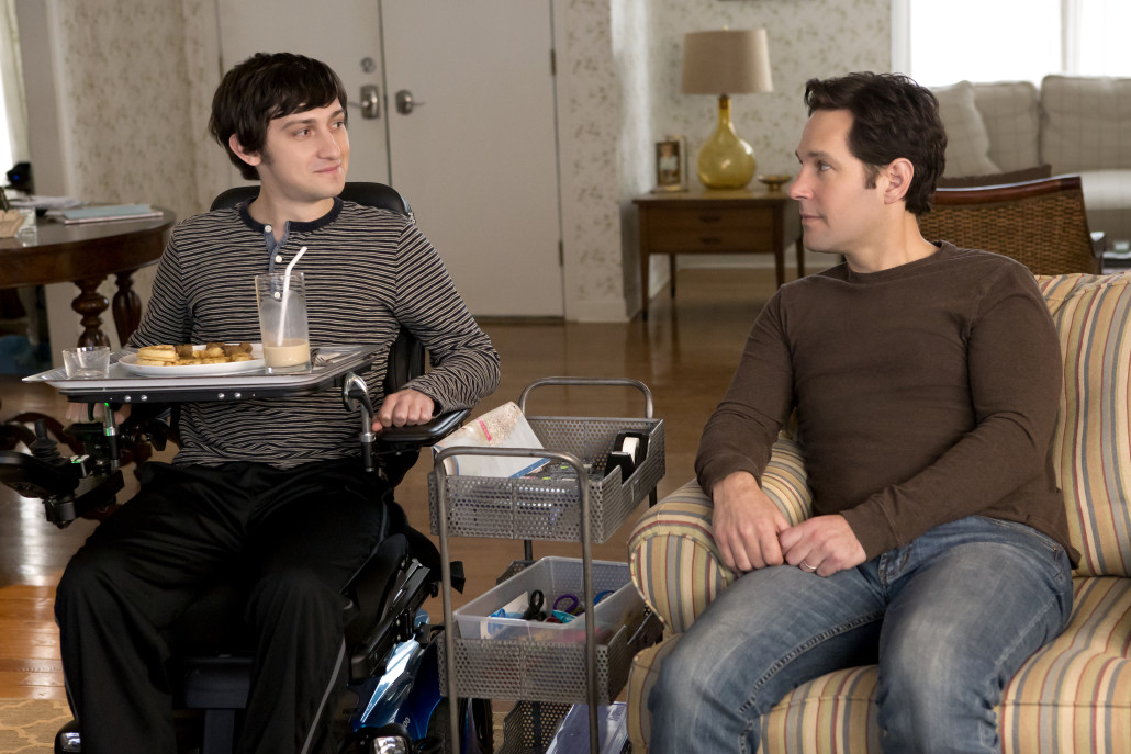 Trevor and Ben sitting in the living room in the movie The Fundamentals of Caring.