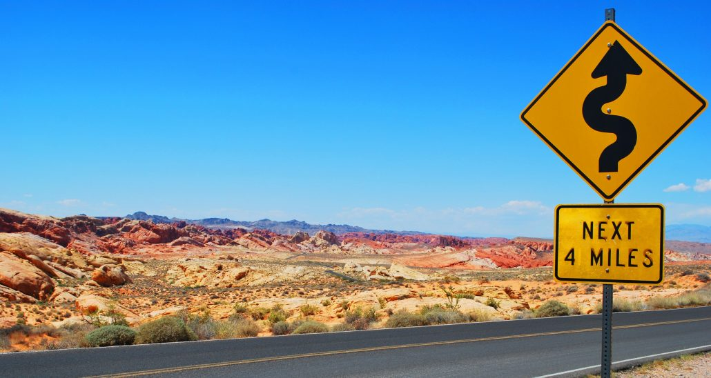 Lonely desert road with a sign showing curves ahead.